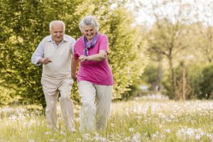 Playful senior couple having fun in nature while chasing.